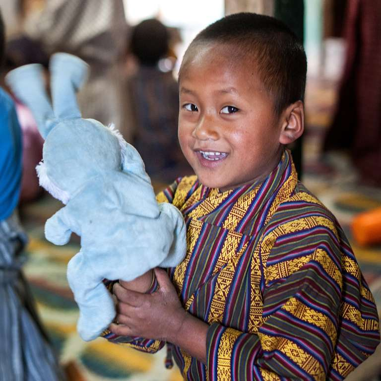 Pema smiles for the camera and holds up a rabbit stuffed animal. He and his friend Chimi are using their imaginations in a learning corner, set up at a preschool in Bhutan. The Red Nose Day Fund helped Save the Children improve the quality of education in more than 200 preschools in Bhutan, training teachers to incorporate play-based math and reading activities that help increase school readiness. Photo credit: Susan Warner/Save the Children, March 2016.
