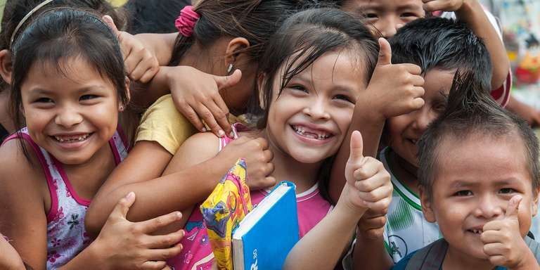 "A group of smiling Bolivian children give a big ""thumbs up"" at an Early Childhood Development program in the village of San Ignacio de Mojos, Bolivia. There are 57 students in the school. Photo credit: Susan Warner/Save the Children, March 2016."
