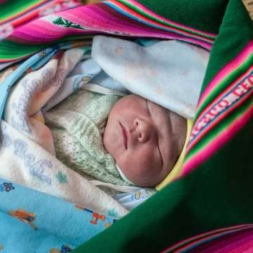 "Baby Emanuel, just 1 day old, is healthy and wrapped in a colorful ""aguayo"" blanket made from llama wool."