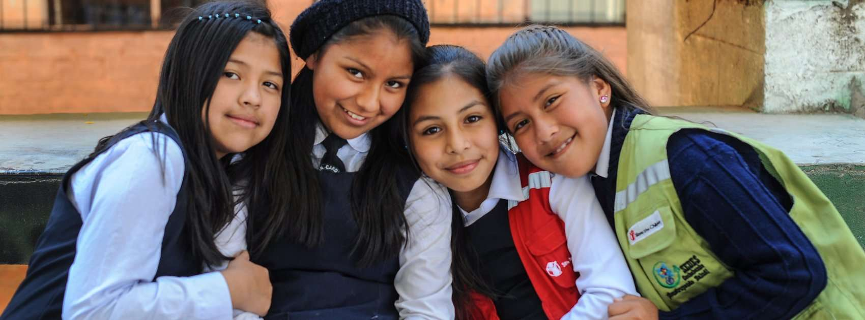 Girls pose for a photograph at a school supported by Save the Children sponsorship programs. Save the Children is working hard in Bolivia to help kids stay healthy and stay in school through sponsorship programs at local elementary schools and early education centers. Photo Credit: Susan Warner/Save the Children 2015.