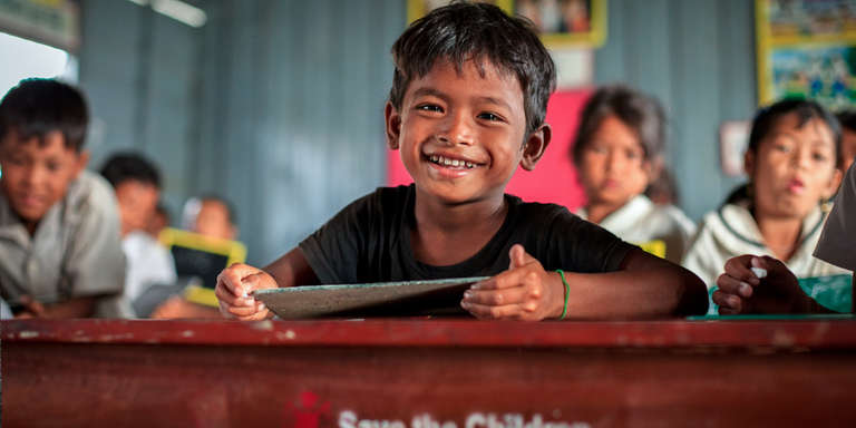 A 6-year-old boy smiles brightly from his classroom in Cambodia. There, Save the Children works with the Provincial Education office to strengthen access to schools and improve the quality of education, giving technical support, and providing materials and furniture to schools. Photo Credit: KJ Borja/Save the Children, March 2013.