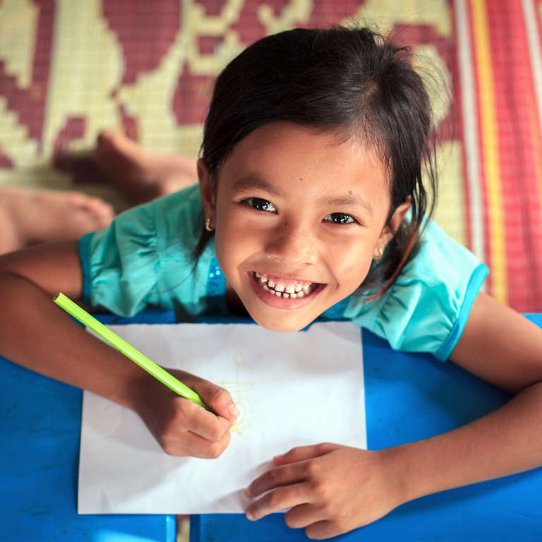 A 5-year-old Cambodian girl looks up from her drawing and smiles happily inside the Sala Khum Early Childhood Development Center. Photo Credit: KJ Borja/Save the Children, April 2013.