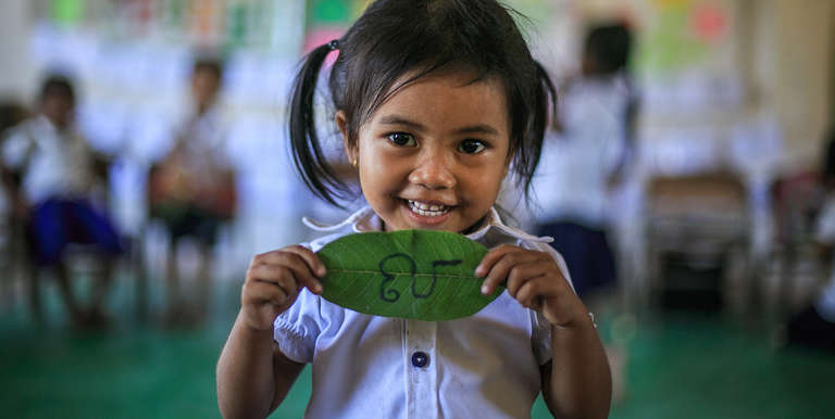 3 year old preschool student holding up a khmer alphabet during a game that boosts literacy. Photo Credit: Kj Borja/Save the Children 2015