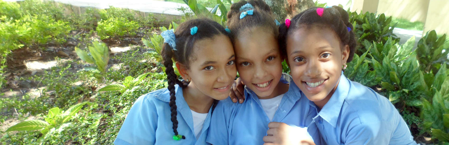 Three school-aged girls attend a Save the Children program at a school in Dajabon, Dominican Republic. Photo credit: Aneliya Nikolova/Save the Children, July 2016.