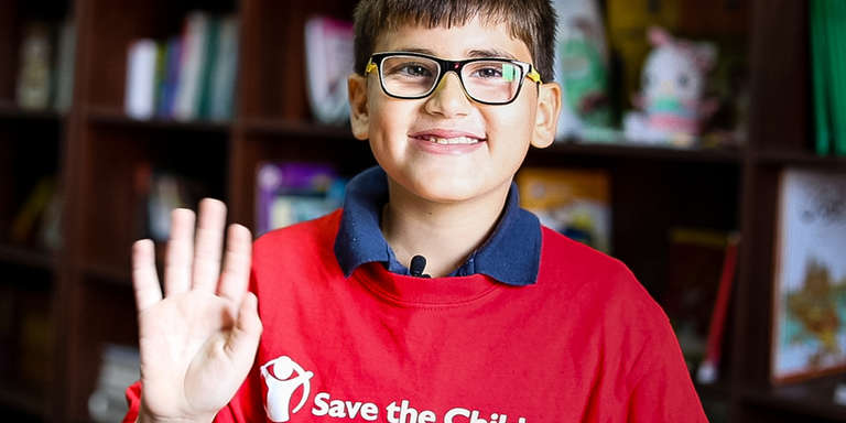 An 11-year old boy from Egypt waves hello, wearing a bright red Save the Children t-shirt and his glasses. A Syrian refugee, now living in Egypt, he dreams of becoming an ophthalmologist one day. Thanks to Save the Children's refugee sponsorship program, both short-term and longer-term needs of vulnerable refugee children and their families are addressed. Photo credit: Victoria Zegler/Save the Children, October 2017.