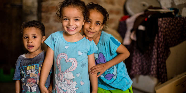 Three Egyptian children – a 2-year-old left, a 3-year-old in the center, and a 7-year-old at right – hold hands and smile for the camera, inside their uncle's home in Egypt. Photo credit: Victoria Zegler/Save the Children, October 2017.