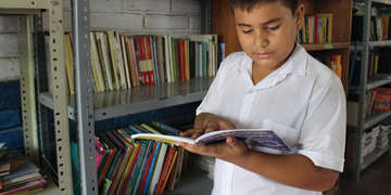 Eduardo, a sponsored child in El Salvador, in a school library reading his favorite book. Photo credit: Save the Children, August 2016.