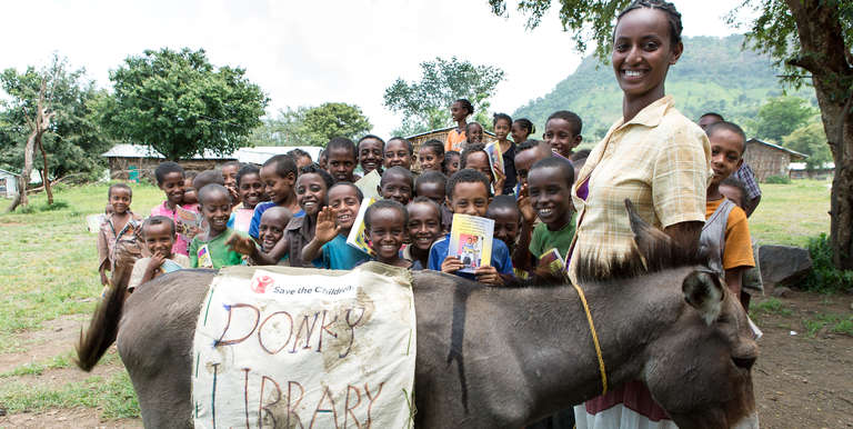 Birtukan Chebud stands with her donkey that has brought books to the children of a nearby village as part of Save the Children's Donkey Library project in Ethiopia. Save the Children's basic education program in Ethiopia has also built and equipped more than 120 elementary schools, benefiting over 1.5 million children. Photo Credit: Save the Children 2015.