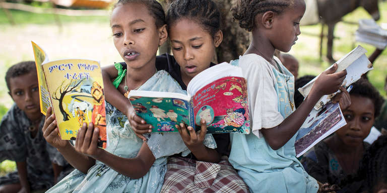 Samrawit, 9, Mahlet , 9, and Belaynesh, 8 read together during a weekly session of Save the Children's Donkey Library project in Ethiopia. Donkeys have traditionally been used by communities in the Amhara region for transporting bulky goods, but this innovative donkey library program has shown communities that donkeys can be used to carry books to help educate children and increase literacy. Photo credit: Save the Children, June 2015.
