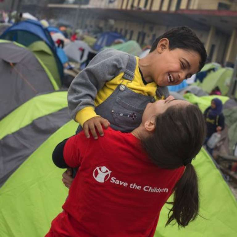 A young child refugee from Syria laughs and plays with Save the Children's Mariluz Garcia in Idomeni at the border between Greece and the Former Yugoslav Republic of Macedonia. More than 10,000 refugees are stranded in Idomeni waiting for the border to open. Save the Children works in Idomeni offering protection to children traveling alone and provides food and support to families. Photo credit: Pedro Armestre, September 2015.