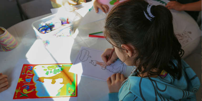 Rula*, 7, draws pictures at Save the Children's child-friendly space in Kara Tepe. She and her family fled from Syria to Turkey, from where they got on a rubber boat to Lesvos island, Greece. Photo credit: Simine Alam/Save the Children 2015.