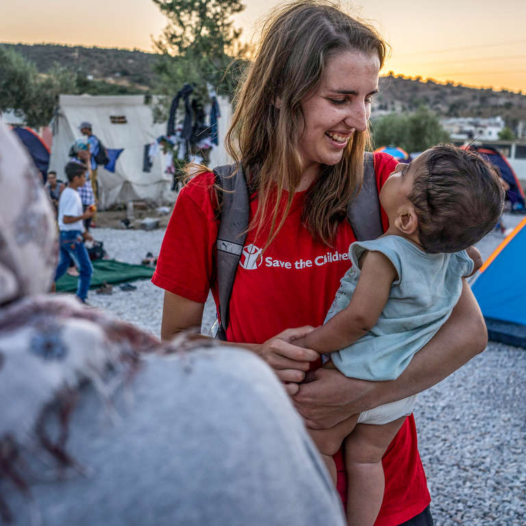 Kate O'Sullivan, communications manager for Save the Children in Greece speaks with a Syrian family from Homs in the informal camp in Kara Tepe, Lesvos. Photo Credit: Anna Pantelia/Save the Children 2015.