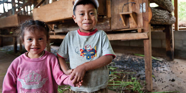 Aida, a 2-year-old girl and her brother Arial 5, hold hands in front of their family goat compound in Guatemala. Many Mayan children are chronically malnourished and six inches shorter than they should be. Photo credit: Susan Warner/Save the Children, July 2013.