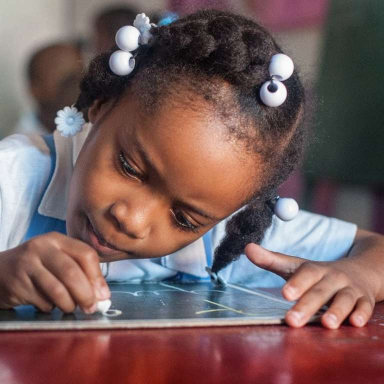 A young student practices letter writing in her preschool classroom in Port au Prince, Haiti. Save the Children worked to help Haiti rebuild its educational system and infrastructure following the destructive and deadly natural disasters. Photo Credit: Susan Warner/Save the Children 2016.