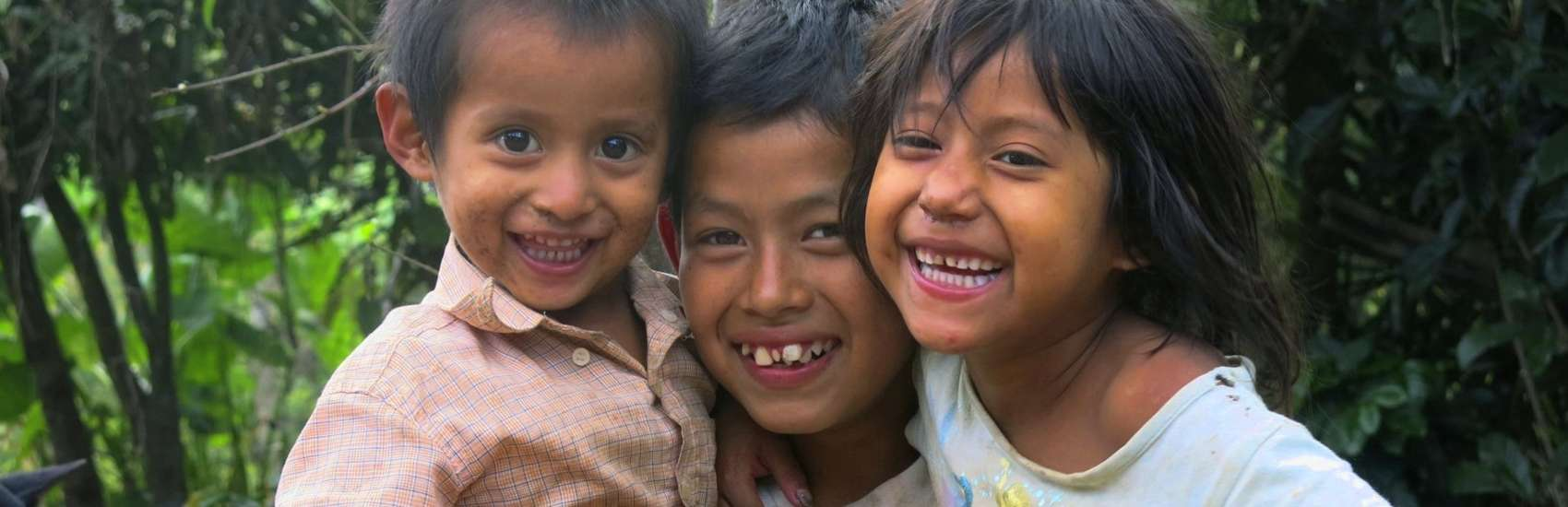 Kevin (age 11) with two of his seven siblings. The nine children are being raised by a single mother, their father left. Kevin is no longer at school as his mother can't afford the costs. He helps his mother when he can, picking tomatoes or cutting coffee if they can find work due to the coffee rust – a blight that is killing coffee plants. The younger siblings are losing weight; the youngest has severe diarrhea due to poor hygiene and no sanitation. Save the Children Honduras is helping this family with bananas and other emergency food packages. Photo credit: Save the Children, June 2014.