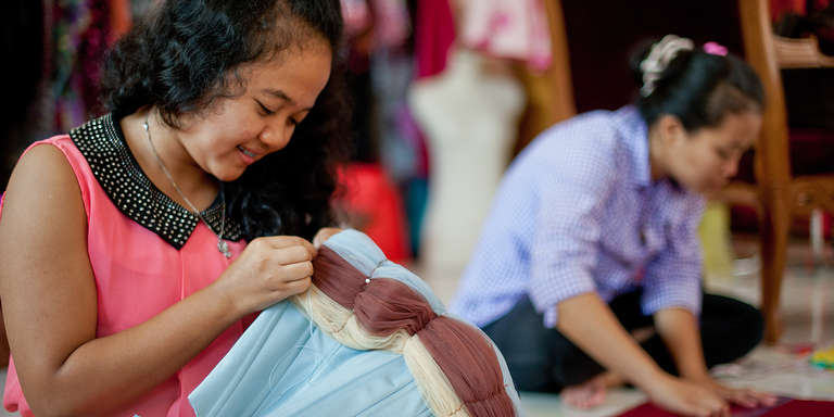 An 18 year-old young woman works on a custom dress at the Princess Jasmine Boutique. She completed a 2 month training at the International Garment Center and an internship for one month. This is her first job. Photo Credit Susan Warner/Save the Children 2014.