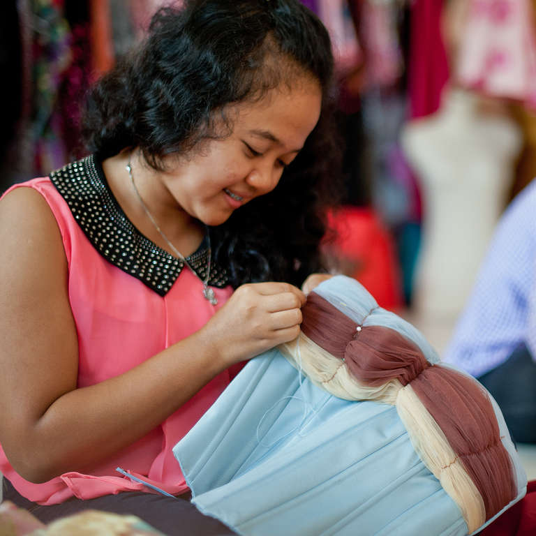 An 18 year-old young woman tailors a custom dress at the Princess Jasmine Boutique in Lampung Indonesia. As part of Save the Children's Skills to Succeed program, she completed a 2-month training program at the International Garment Center and an internship for one month. This is her first job. Photo Credit Susan Warner/Save the Children 2013.