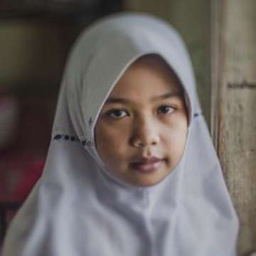 An 11-year old girl, Febi, stands before a window at the orphanage where she lives in Bandung Province, Indonesia. She and her brother Ahmad were sent to the orphanage when their parents lost their income and couldn't afford to send her them school. In Indonesia, up to half a million children grow up in orphanages – the highest proportion of any country in the world. Yet nine out of ten children growing up in care homes have at least one parent living. Many struggling parents give up their children, believing it's the only way to give them a better future – although growing up in an orphanage leaves children vulnerable to abuse. Care homes in Indonesia are largely unregulated, operating for profit, not for the children's best interest. Photo credit: CJ Clarke/Save the Children, July 2014.