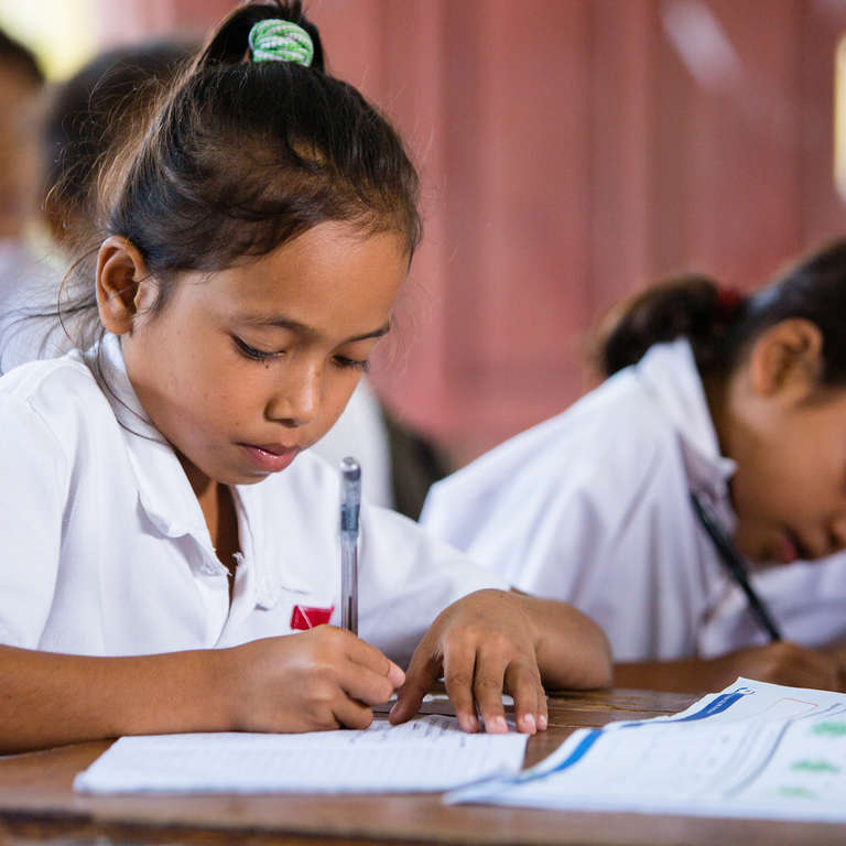 9-year-old Angelika completes an in-class writing activity with learning materials provided by Save the Children. She began sponsorship in 2015, where she has since learned the importance of a healthy lifestyle allowing her to not come to school sick, or miss class due to illness. Photo credit: Victoria Zegler/Save the Children, July 2017.