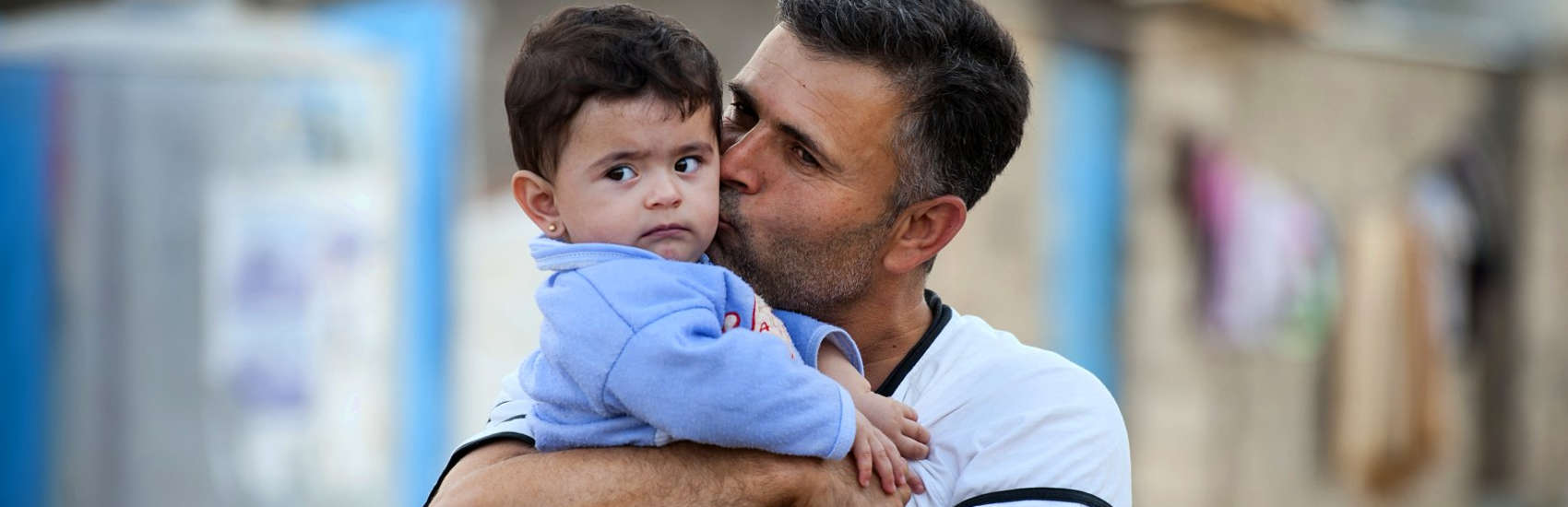 A fourteen month-old boy get a kiss from his father at a refugee camp. Hundreds of thousands of refugees and internally displaced families have fled the violence across Iraq and Syria. Children in Iraq have often witnessed or experienced violence, and left their homes in terrifying circumstances. Many now face hot summers and freezing winters living in tents, half built apartment blocks and public buildings. Save the Children is providing essential goods to families, such as water and hygiene kits, as well as building sanitation facilities and running child friendly spaces and education classes. Photo credit: Sebastian Rich/Save the Children, October 2014.