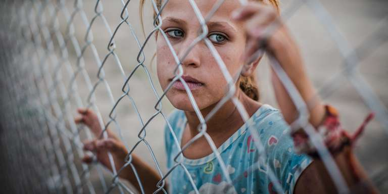 A young girl stands behind a fence at a refugee camp. She and her family are among the 3.1 displaced people in Iraq. Due to armed conflict the family of eight, were forced to leave their home and flee. Photo Credit: CJ Clarke/Save the Children 2015.