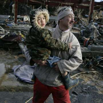 A Japanese man, holding his 6-year-old son, walks through streets filled with debris after two tsunami waves devastated their town of Onigawa, Japan in 2011. They escaped, but their home was hit by a 10-meter high wave; nothing was left of it.  Photo credit: Jensen Walker/Save the Children, March 2011.