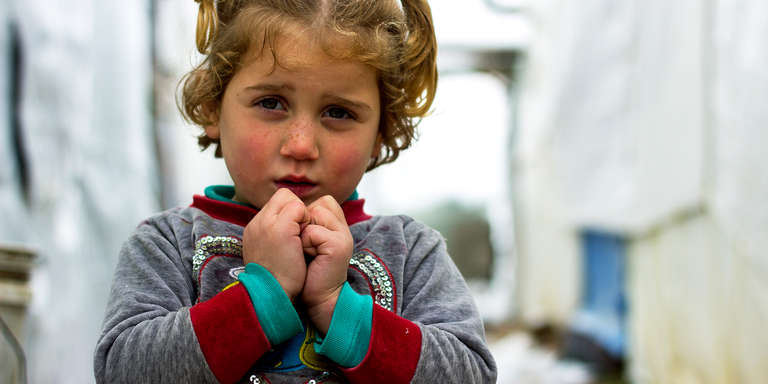 Tamara*, a Syrian refugee, shivers in the cold outside her family's shelter at an informal settlement in Lebanon. Photo credit: Ahmad Baroudi/Save the Children, March 2015.