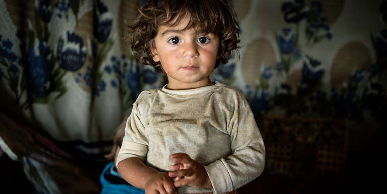 A toddler, in her home – a tented refugee settlement in Lebanon, near the Syrian border. Photo credit: Save the Children, April 2014.