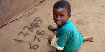 A boy practices writing numbers on the ground at primary school in Malawi. Photo Credit: Amos Gumulira/Save the Children 2011.