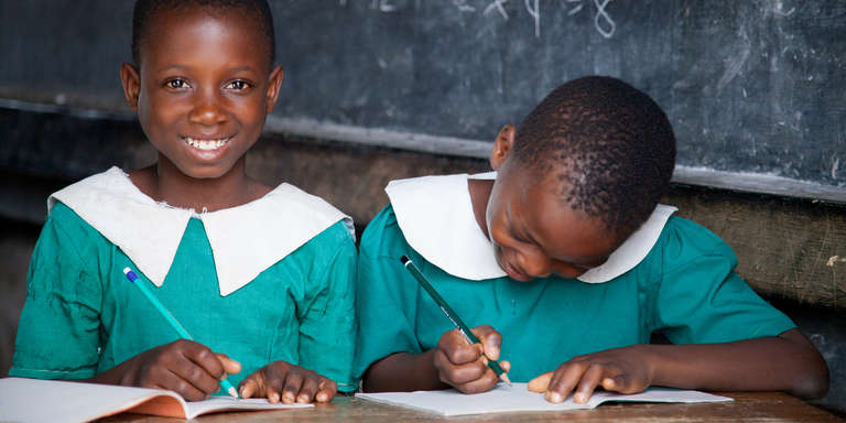 Two schoolgirls with pencils and notepads smile from their classroom in Malawi. Photo credit: Jordan J. Hay/Save the Children, 2017.