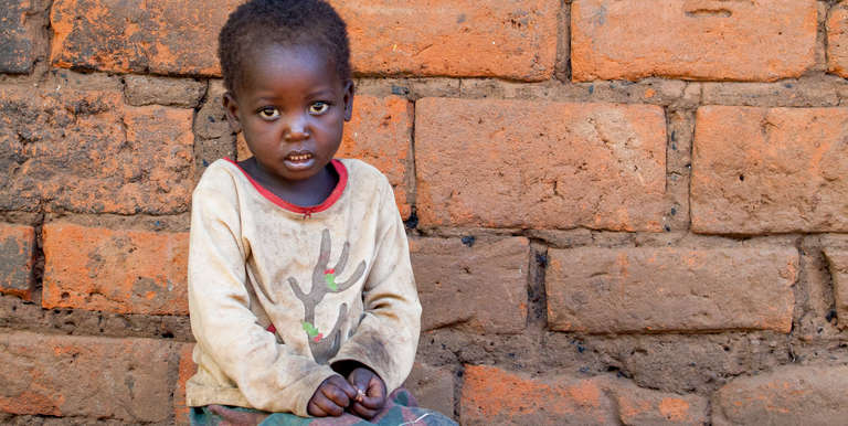 A 4-year old child, barefoot and dirty, sits on the packed-dirt ground in Zomba, Malawi. Photo credit: Jordan J. Hay/Save the Children, April 2017.