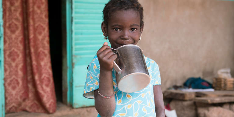 A five-year-old girl, Satou, drinks from a cup outside her home in Mali. She knows that when she's thirsty, she should run all the way home to get a clean drink of water. Photo credit: Save the Children, December 2017.