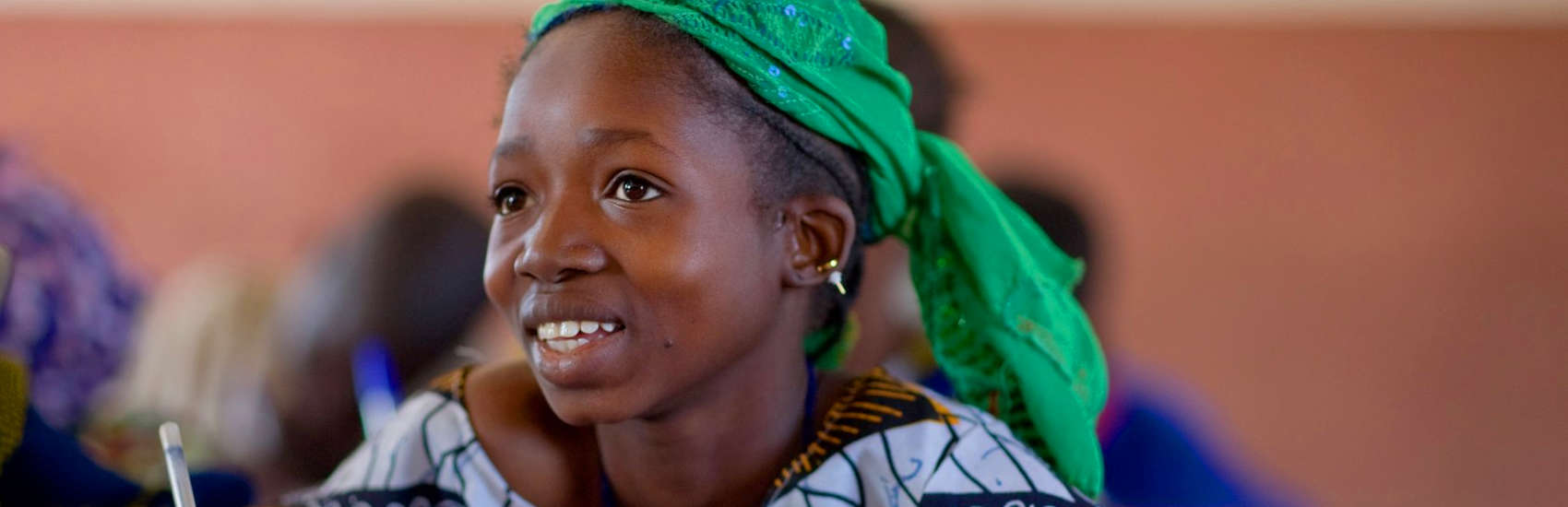 A young girl in a bright green head wrap sits at her school desk, ready to learn in Tabarako Town, Sikasso District, Mali. Photo credit: Joshua Roberts/Save the Children, January 2010.