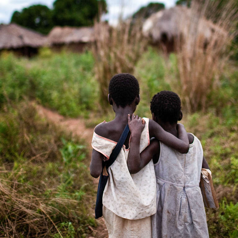 Two young sisters who lost their mother to HIV and AIDS walk home arm-in-arm after school. Photo credit: Save the Children, 2010.