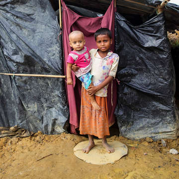 A six-year old boy holds his one-year old brother as they stand outside the makeshift tent in Cox's Bazar district, Bangladesh where they live.