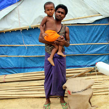 A father holds his two-year-old son in front of a makeshift hut in a Rohingya refugee camp in Cox's Bazar, Bangladesh. He and his wife fled  Myanmar in August 2017, when violence escalated. The family walked for seven days to get to Bangladesh, and when they arrived, the child was extremely sick with diarrhea. Photo credit: Daphnee Cook / Save the Children, May 2018.