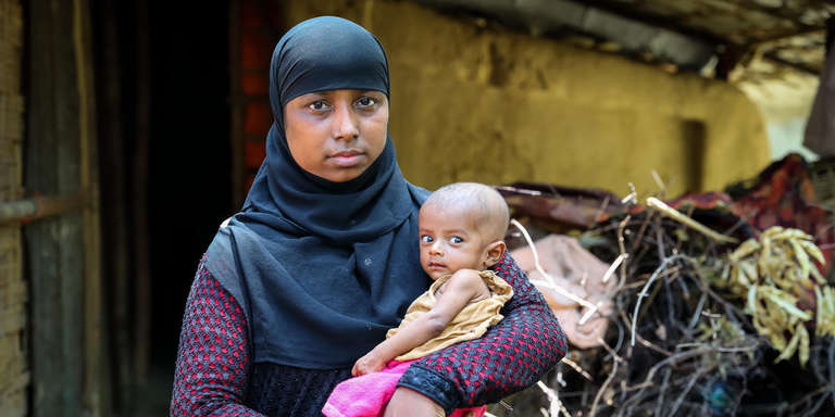 Kismot – a 25-year-old mother of three – is shown here, holding her seven-month-old daughter Jamila. Kismot, her husband and two other children – Rohingya refugees – have lived in the Leda Camp in Cox's Bazar since last October. Kismot gave birth to Jamila in the camp after the family arrived. Photo credit: GMB Akash  /  Save the Children, June 2018.