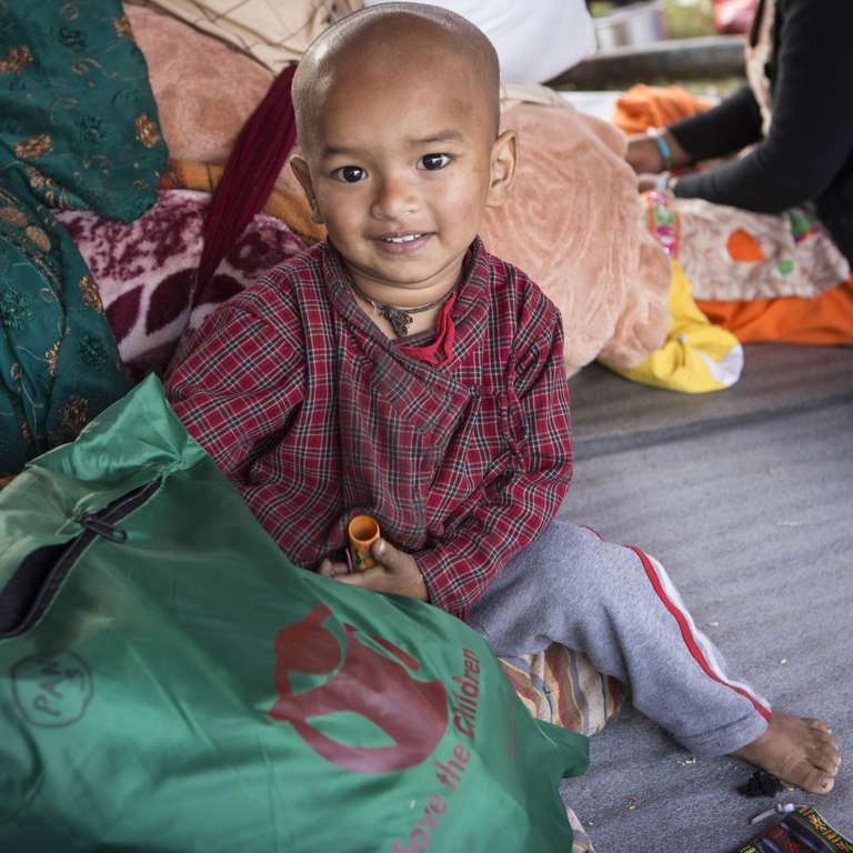 Jason, age two, pictured at a tented settlement in Kamalbinayak, Bhaktapur, Nepal. Save the Children provides displaced Nepalese families with essential items to help keep them healthy, safe and warm. Photo credit: Jonathan Hyams/Save the Children, April 2015.