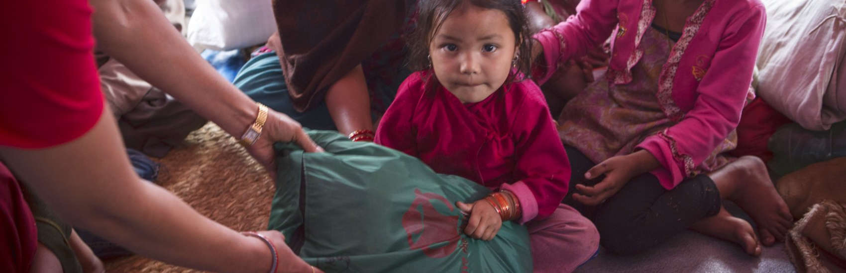 Aswini, age four, lived with her family in a tent settlement in Nepal after the earthquake. Save the Children provided displaced families, including Aswini's, essential items including infant kits, warm clothes, hats and blankets as well as hygiene kits. Photo credit: Jonathan Hyams/Save the Children, April 2015.