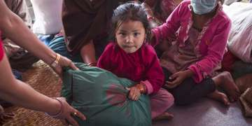 A girl from Nepal sits in her home