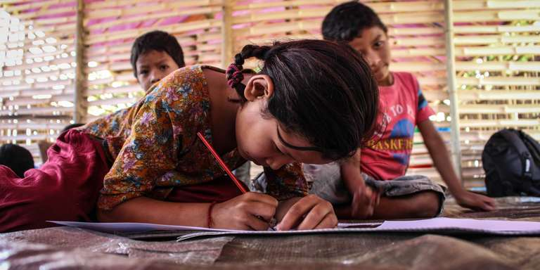 A Nepalese studies at a temporary learning center built by Save the Children. Her school was badly damaged and was not usable for teaching. Save the Children worked with the community to build a temporary learning center, which was completed, and used to teach students, a week before the official Back to School date. Photo Credit: David Hartman/Save the Children 2015.