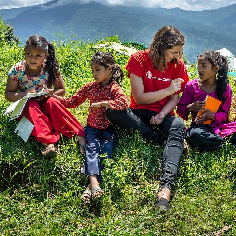 Kate O'Sullivan draws pictures with Nepalese children as they sit outside a village that was badly hit by the 2015 Nepal Earthquake. The earthquake took away lives, homes, and livelihoods, and put the children here in further jeopardy of trafficking. Photo Credit: Save the Children/Suzanne Lee 2016.