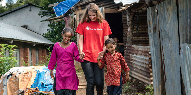 Kate O'Sullivan walks in front of child's makeshift home that was built using tin sheets after the earthquake destroyed her house in Sangachok Nepal. Photo Credit: Suzanne Lee/Save the Children 2016.