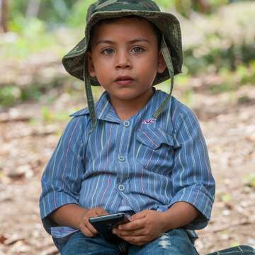 Young Christopher plays with a borrowed cell phone. He lives in Nicaragua, where his parents participate in a livelihoods program through Save the Children. They started producing vegetable seedlings and eventually turned profits and purchased more land. They also improved their family's nutrition because they received support to grow corn and beans. Photo credit: Susan Warner/Save the Children, August 2016.