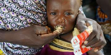 An infant of 9 months, with her mother Alima, eats high nutrient peanut paste as a distribution at the Guidanaoutchi Clinic, Niger. Photo Credit Save the Children 2016.