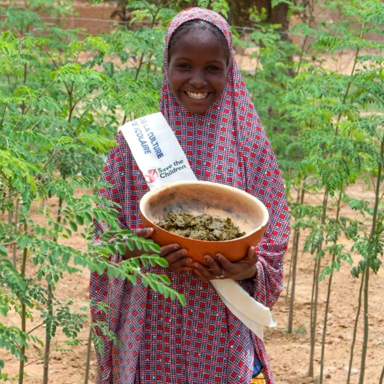 Barira holds a bowl of nutritious moringa grown at her community garden. She leads the fight against child hunger with her local student government. Photo Credit: Talitha Brauer/Save the Children, 2016.