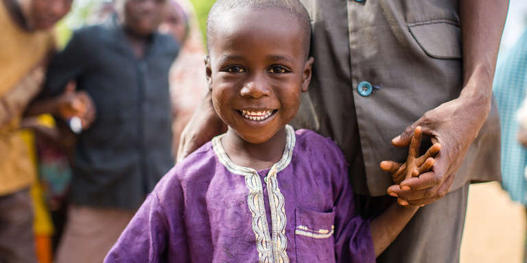 A 6-year-old boy dressed in a bright purple tunic smiles for the camera after an Early Childhood Care and Development class in his community in Maradi, Niger. Photo credit: Victoria Zegler/Save the Children, December 2016.