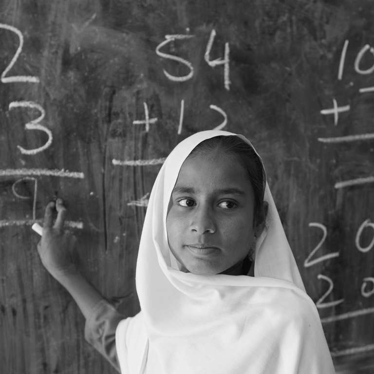 A young student doing math sums on the blackboard in class 3 in a government girls school in Khyber Pakhtunkhwa Province, Pakistan. Photo Credit: Asad Zaidi/Save the Children 2014.