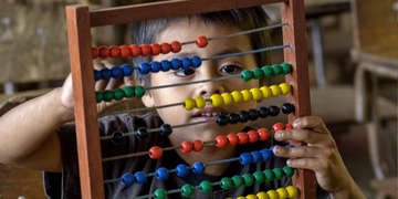 A young boy, age 7, using abacus from Learning Corner Program in his 1st grade class. Photo Credit: Save the Children 2016.