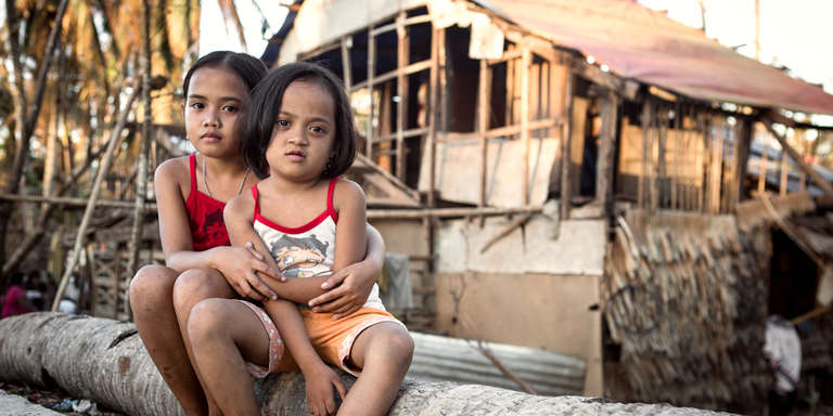 Two young girls sit in front of their home after it was destroyed by Typhoon Hagupit, Eastern Samar. Save the Children provided their family with an emergency shelter kit and other essential items. Photo Credit: Jonathan Hyams/Save the Children 2014.